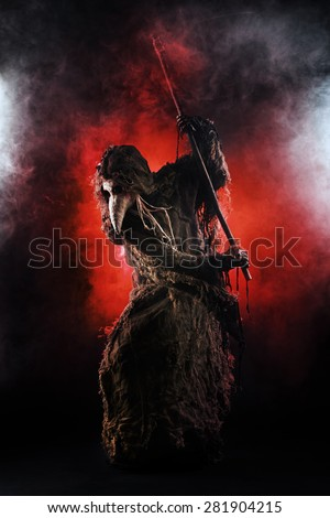 Portrait of a terrible plague doctor with a scythe. Medieval Europe. Horror. Halloween. - stock photo