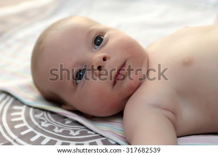 Portrait of a thinking baby boy on a bed - stock photo