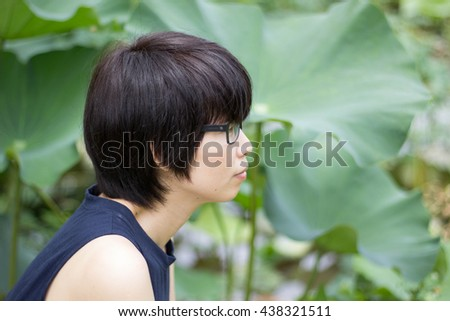 Portrait of a thinking woman looking up in lotus leaves background.