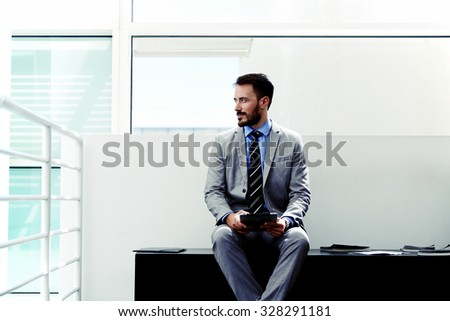 Portrait of a thoughtful businessman dressed in suit holding touch pad while sitting in office space, young man economist in formal wear thinking about something while work on his digital tablet  - stock photo