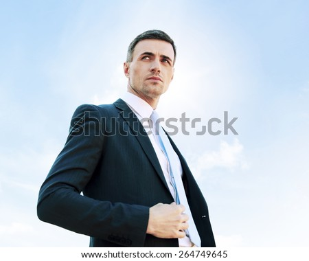 Portrait of a thoughtful businessman on blue sky background - stock photo