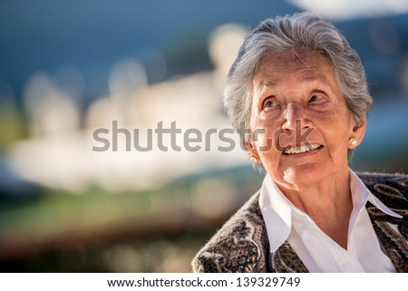 Portrait of a thoughtful elder woman looking up - stock photo