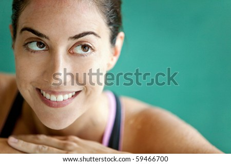 Portrait of a thoughtful female swimmer smiling - stock photo