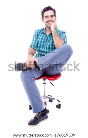Portrait of a thoughtful man sitting on the chair, isolated on white background