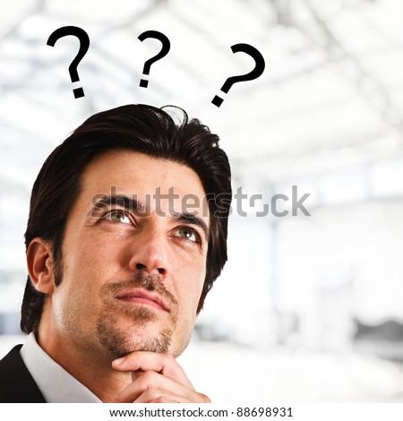 Portrait of a thoughtful man with question marks surrounding his head - stock photo