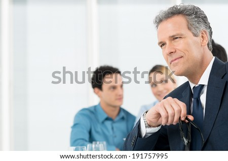 Portrait Of A Thoughtful Mature Businessman Holding Eyeglasses - stock photo