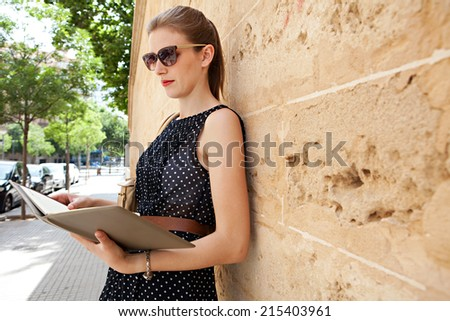Portrait of a thoughtful professional business woman holding and reading a work diary while leaning on an old stone building wall in a classic city, outdoors. Smart professional young woman. - stock photo