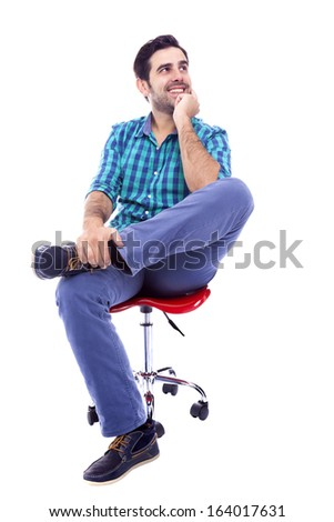 Portrait of a thoughtful smiling man sitting on the chair, isolated on white background - stock photo