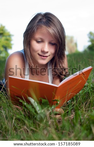 Portrait of a thoughtful teenage girl reading book in the park