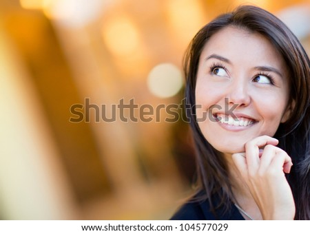 Portrait of a thoughtful woman looking up and smiling - stock photo