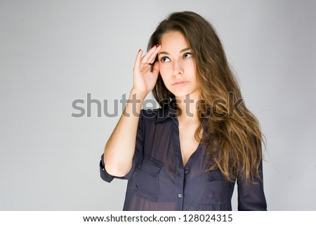 Portrait of a thoughtful worried looking young brunette woman. - stock photo