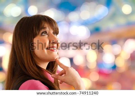 Portrait of a thoughtful young happy woman. Colorful blurred background. - stock photo