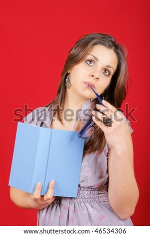 Portrait of a thoughtful young woman holding a book in her right hand and glasses in her left hand. Studio shot over red background.