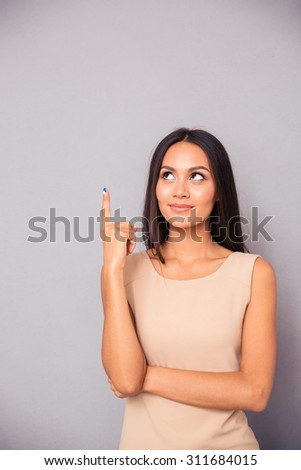Portrait of a thoughtful young woman pointing finger up over gray background - stock photo