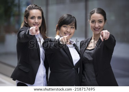 Portrait of a three happy business woman pointing there finger at you.