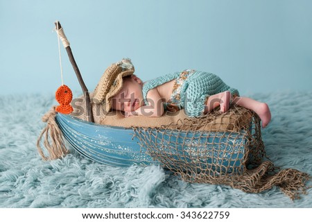 Portrait of a three week old newborn baby boy. He is sleeping in a miniature boat and wearing crocheted overalls and a fisherman's hat. Shot in the studio on an aqua colored flokati rug. - stock photo