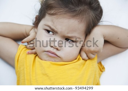 Portrait of a three year old girl with an unhappy face - stock photo