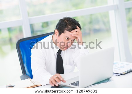 Portrait of a tired businessman looking in laptop - stock photo
