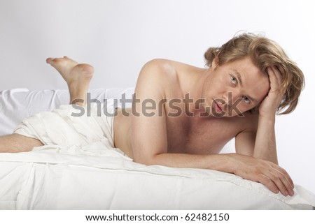 Portrait of a tired handsome man in his bed. Studio shot. See more in my portfolio - stock photo