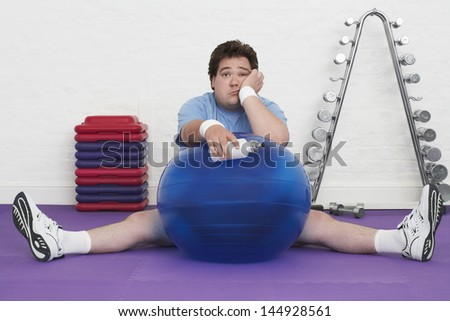 Portrait of a tired overweight man sitting on floor with exercise ball in health club - stock photo
