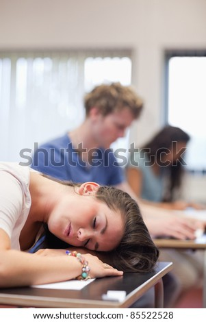 Portrait of a tired student sleeping in a classroom - stock photo