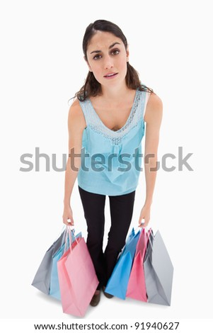Portrait of a tired woman posing with shopping bags against a white background - stock photo