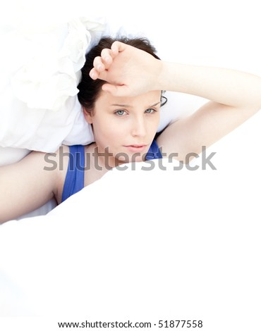 Portrait of a tired woman relaxing in her bed - stock photo