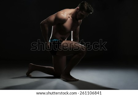 Portrait of a Topless Muscular Man Sitting on the Floor in a Yoga Position Looking at the Camera on a Black Background. - stock photo