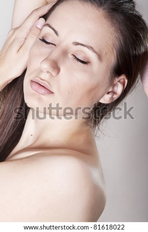 Portrait of a topless sensual woman touching her face and hair on grey background - stock photo