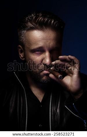 Portrait of a tough guy smoking cigar - stock photo