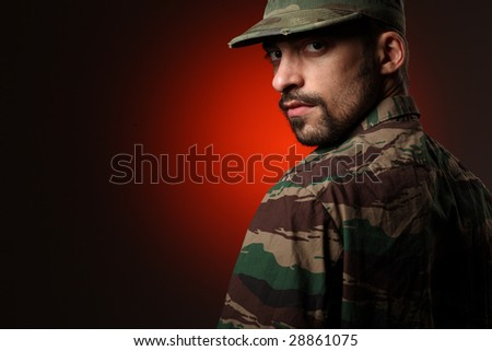 Portrait of a tough soldier looking at camera over his shoulder