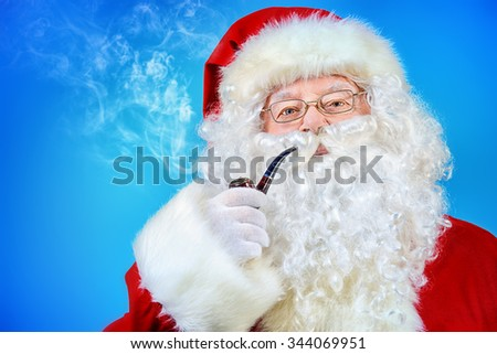 Portrait of a traditional Santa Claus smoking a pipe. Blue background. Studio shot. Christmas. - stock photo