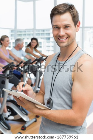 Portrait of a trainer with people working out at bike class in gym