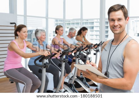 Portrait of a trainer with people working out at spinning class in gym