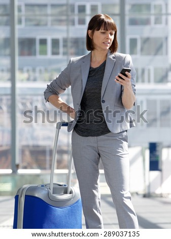 Portrait of a traveling business woman looking at mobile phone  - stock photo