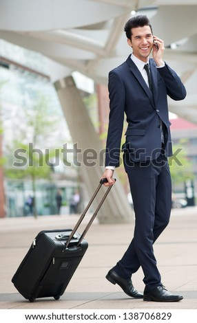 Portrait of a traveling businessman talking on phone outdoors - stock photo