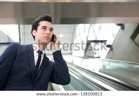 Portrait of a traveling businessman talking on the phone on escalator - stock photo
