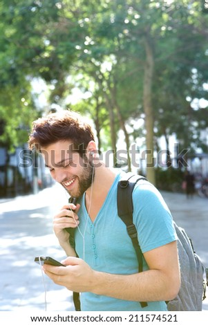 Portrait of a traveling man smiling with backpack and mobile phone - stock photo
