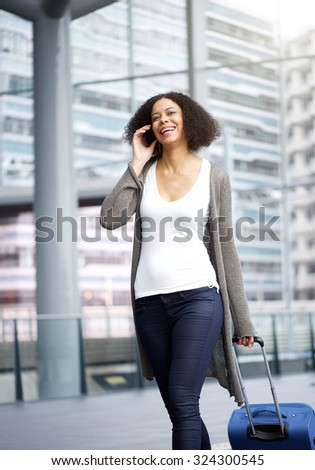 Portrait of a traveling young african american woman walking and talking on cellphone - stock photo