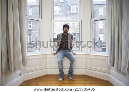 Portrait of a trendy Asian man at home. Indian man relaxing at home.