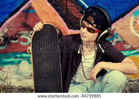 Portrait of a trendy boy teenager with headphones and skateboard outdoors. - stock photo