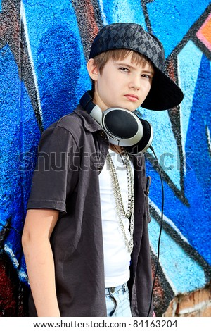 Portrait of a trendy boy teenager with headphones outdoors. - stock photo