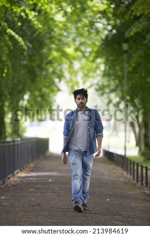 Portrait of a trendy Indian man walking in a city park. - stock photo