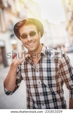 portrait of a trendy young man walking in the street, he wears a hat and sunglasses - stock photo