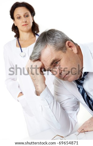 Portrait of a troubled senior man and a woman doctor