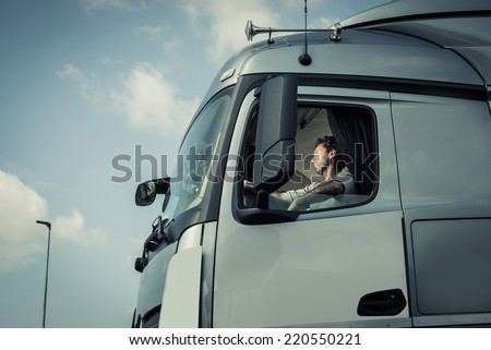 Portrait of a truck driver sitting in cab - stock photo