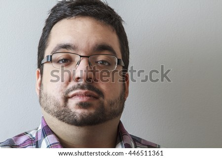 Portrait of a twenty year old man against a white wall