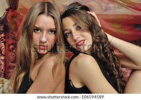 Portrait of a two beautiful women in luxury interior.