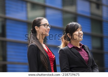 Portrait of a two confident business woman standing outdoors in modern urban setting. - stock photo