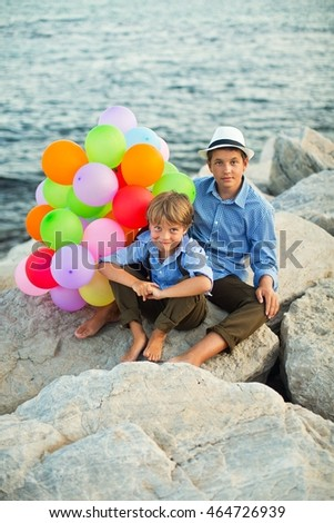 Portrait of a two cute stylishly dressed brothers with balloons on the beach .Outdoor,  summer time photo .